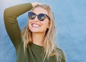 young blonde woman smiling with sunglasses on